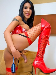 Dickgirl posing sexy in her passion red PVC outfit